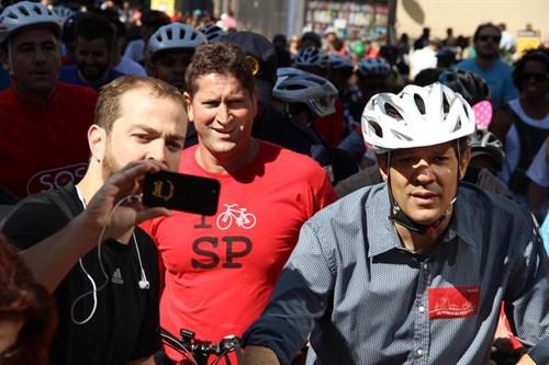 Secretário Jilmar Tatto (de vermelho) e Prefeito Fernando Haddad (de capacete) pedalando na ciclovia da Avenida Paulista.